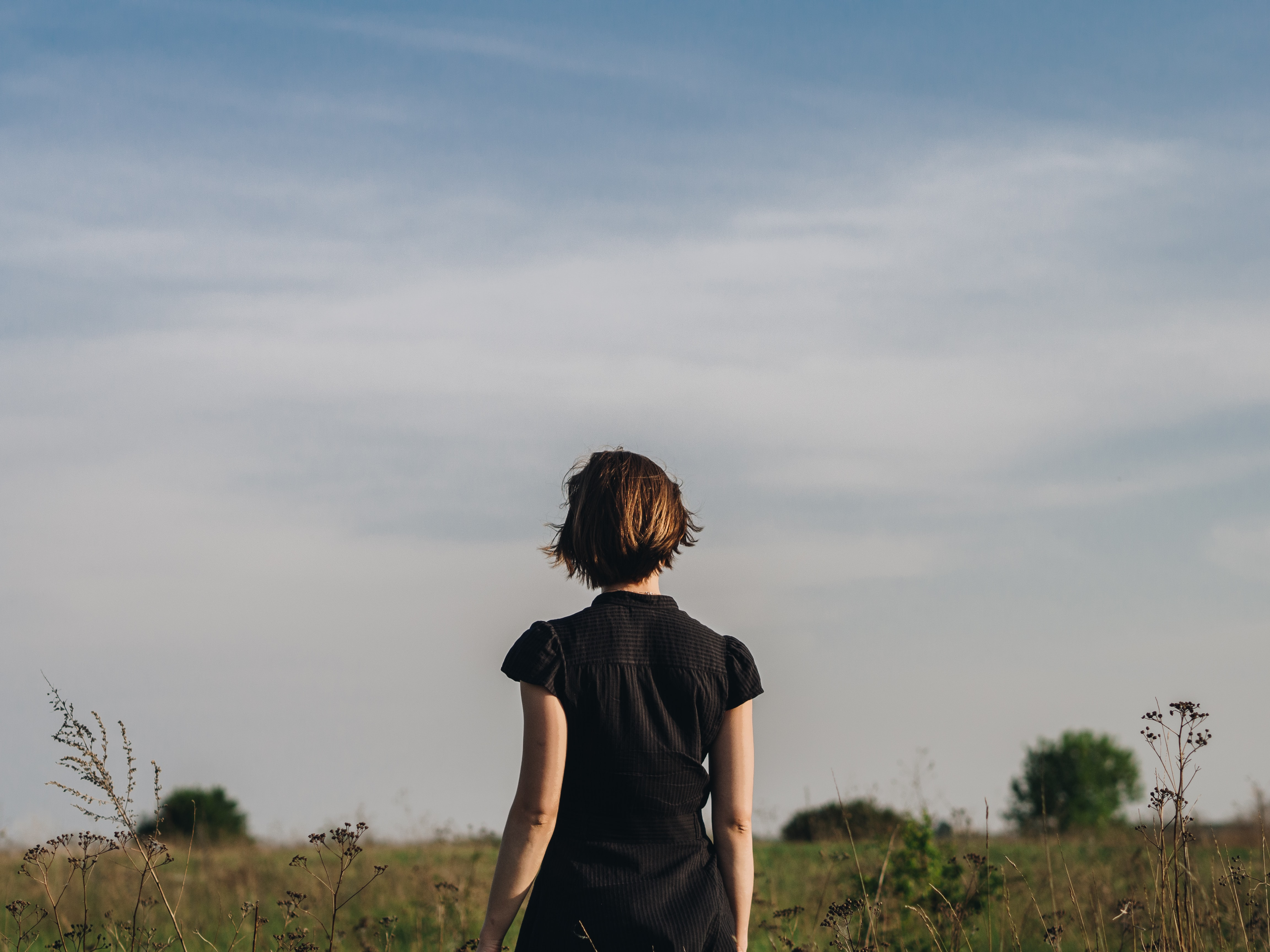 woman in black shirt standing in grass field