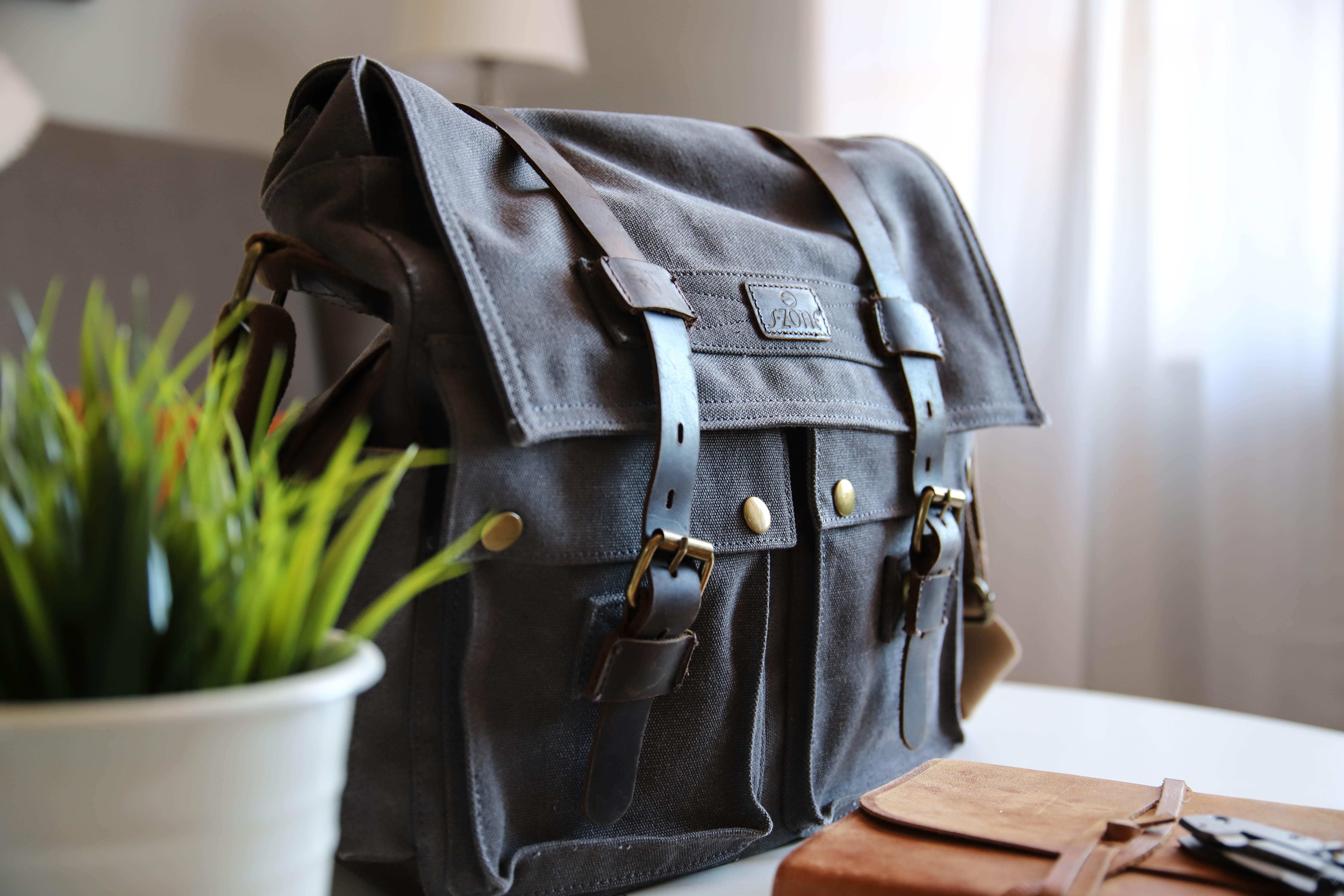 black leather satchel bag on white top
