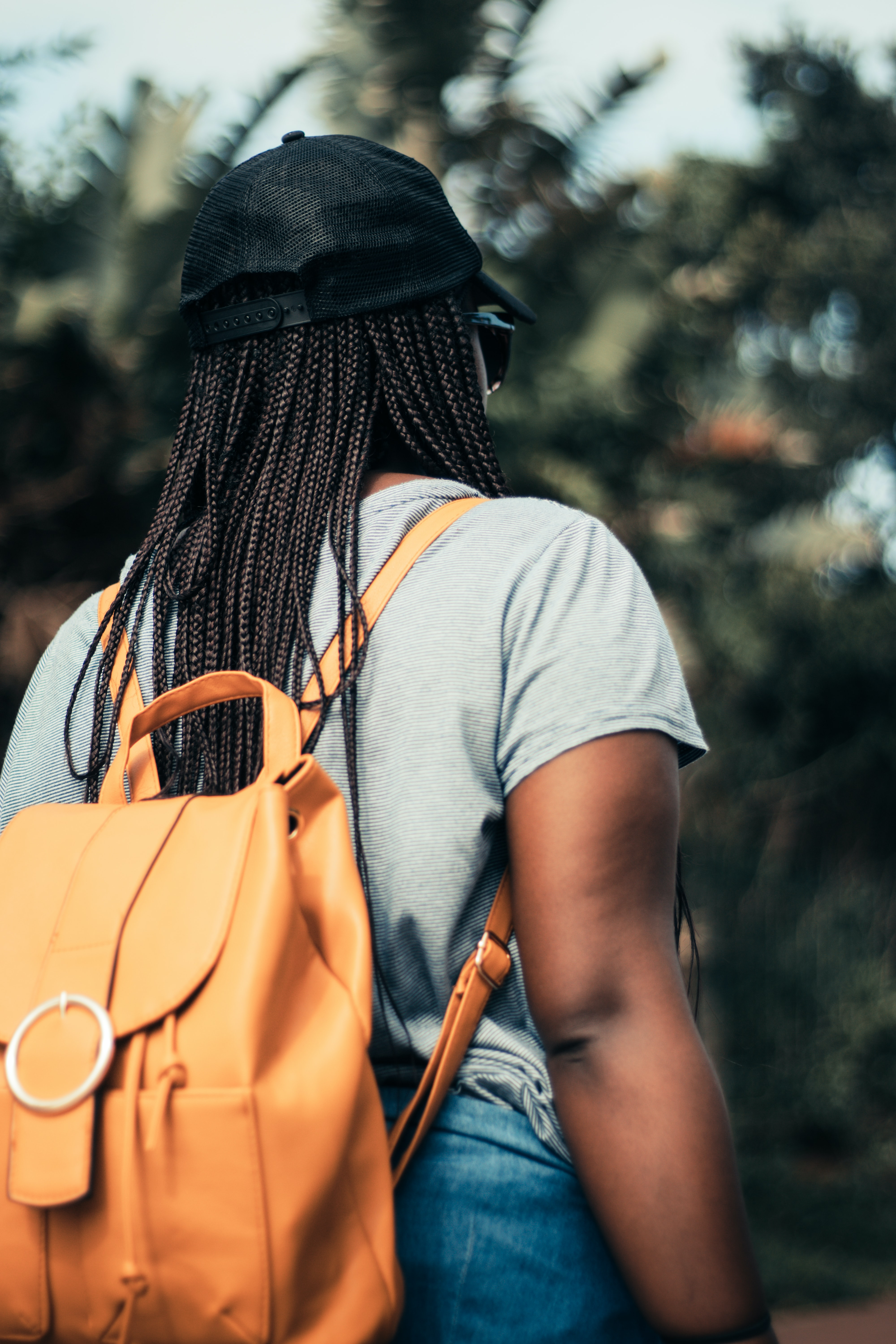 woman with braided hair wearing backpack