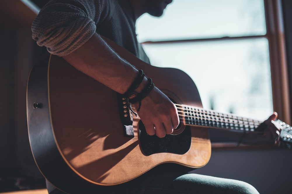 man playing acoustic guitar selective focus photography
