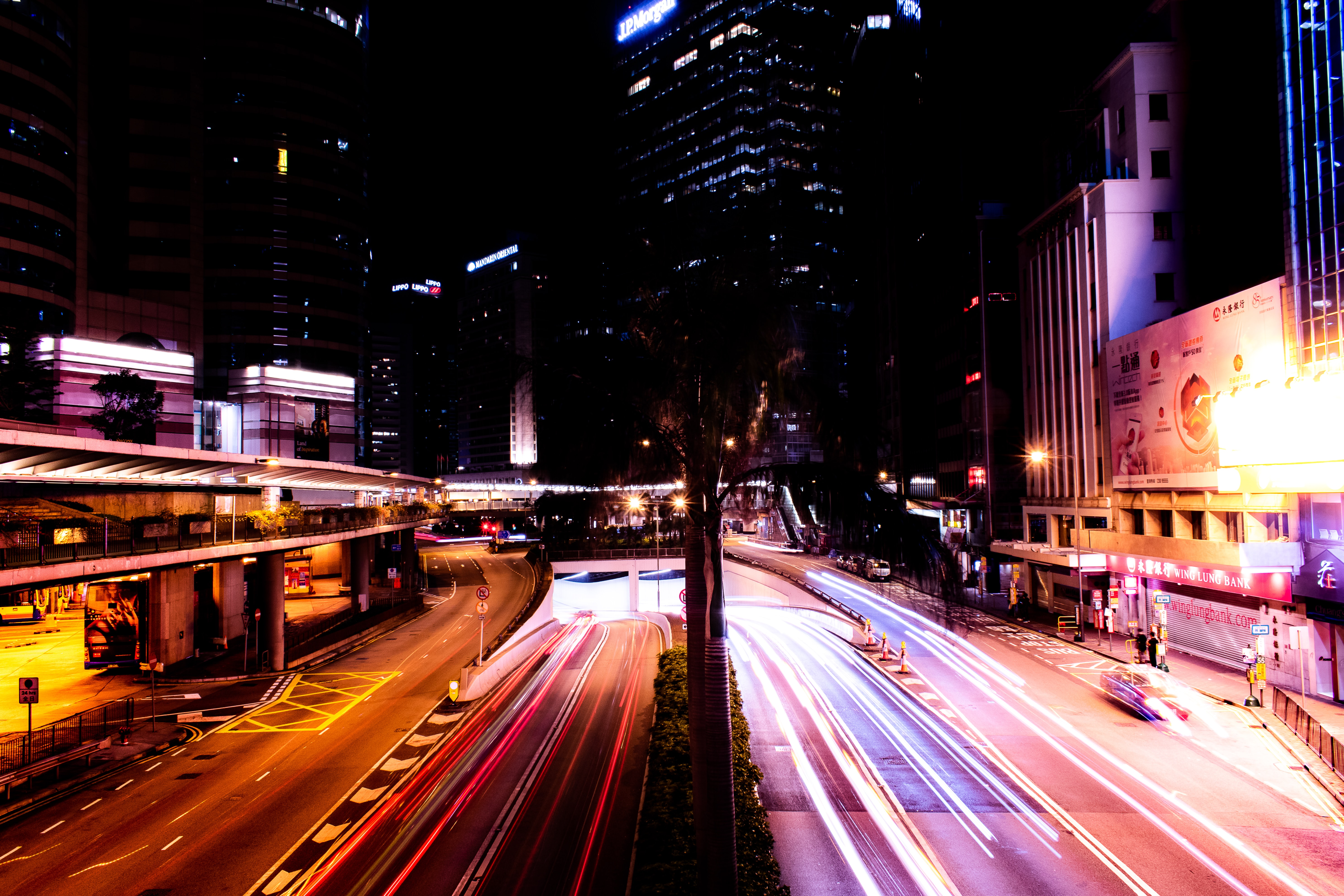 time lapse photography of passing vehicles between high-rise buildings