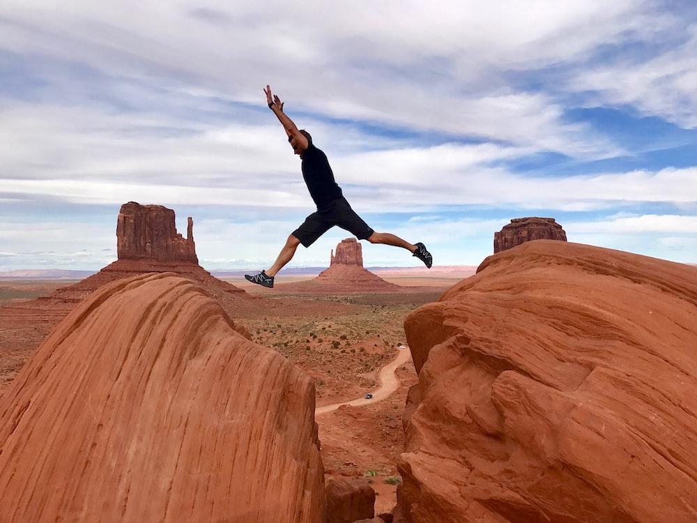 man jumping on canyon