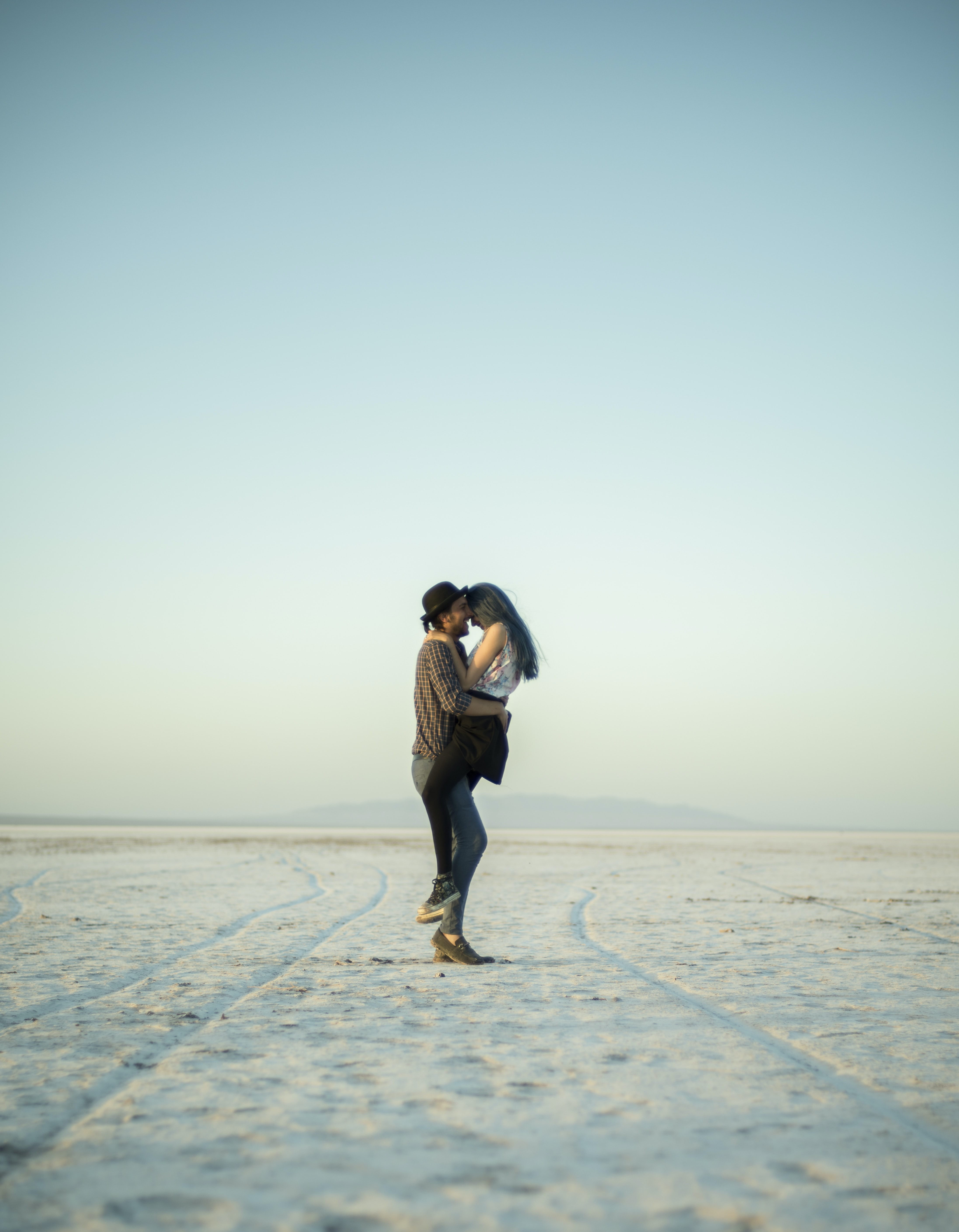 man carrying woman while standing on snow road