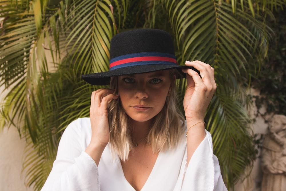 woman wearing black hat beside trees