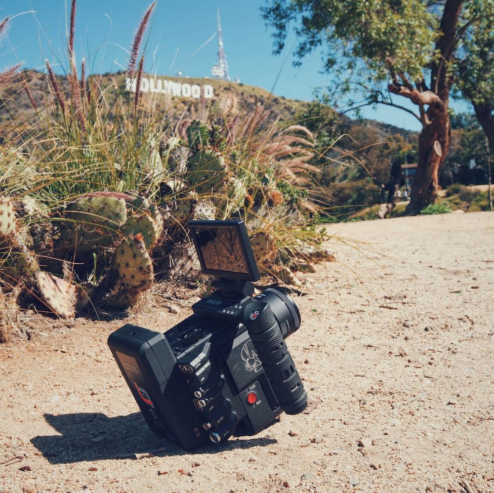 black professional video camera on floor near green grass