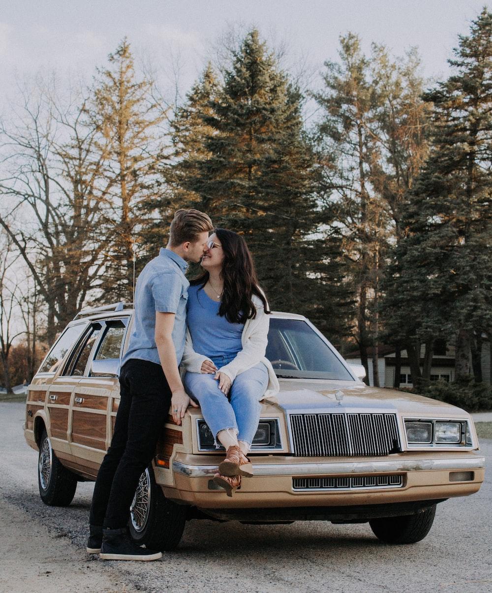 man kissing woman while sitting on brown car