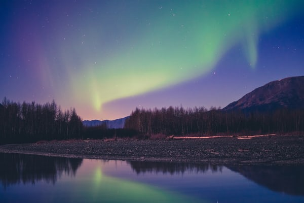 Northern lights in a twilight sky over a river with a rocky bank and pine trees