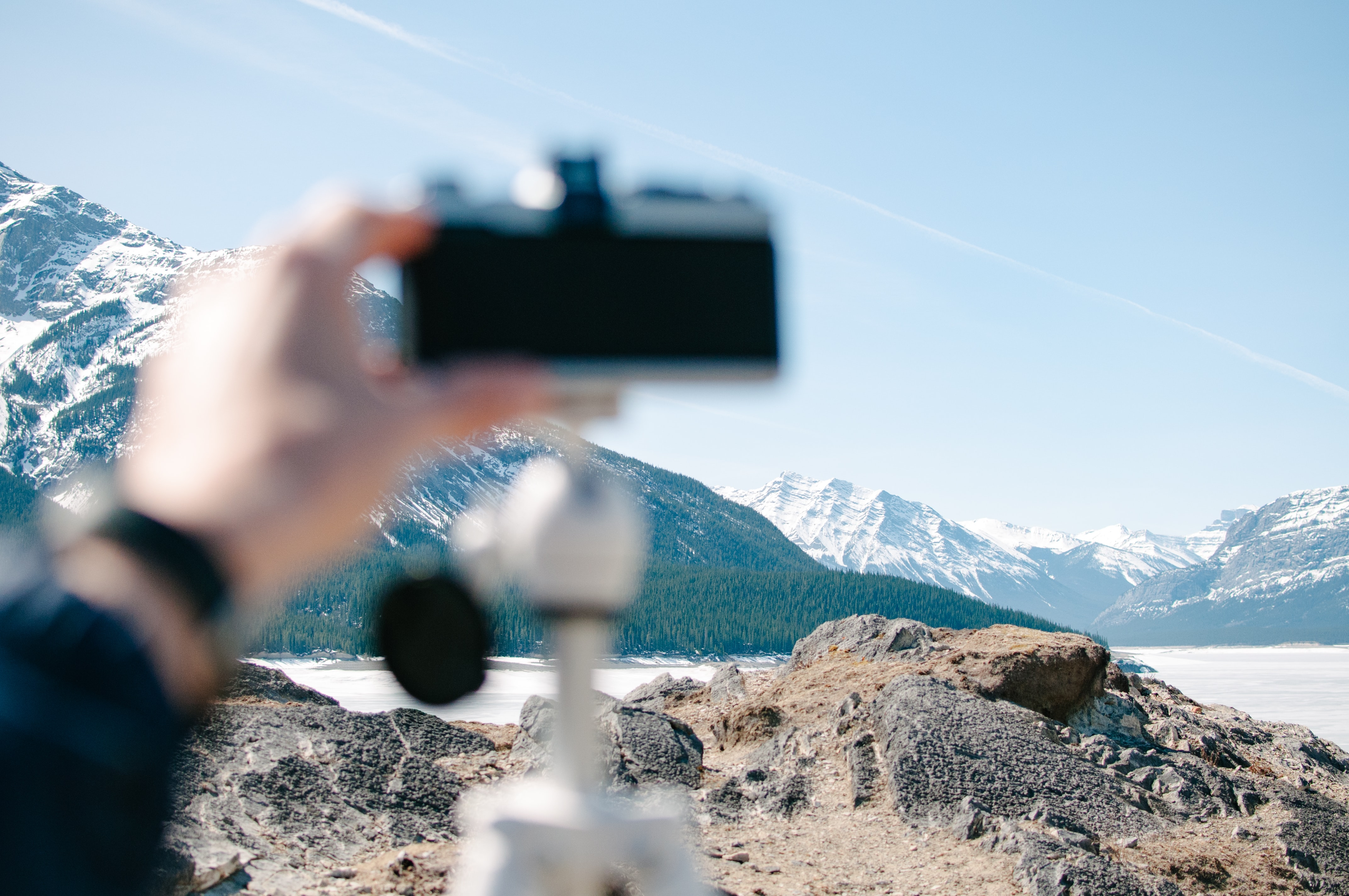 person holding camera distance with white mountains