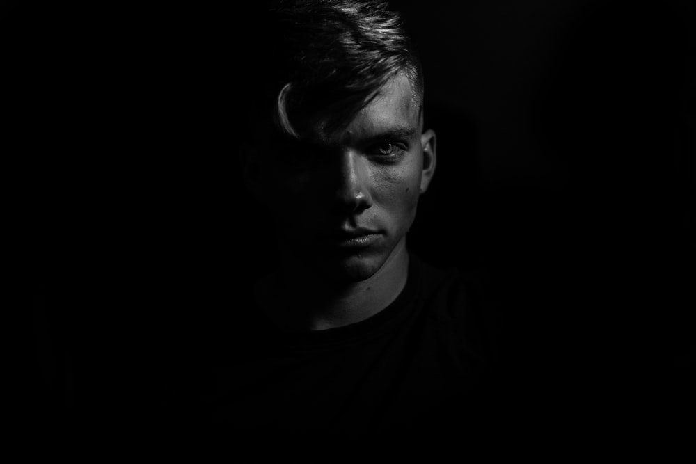 grayscale man in dark room