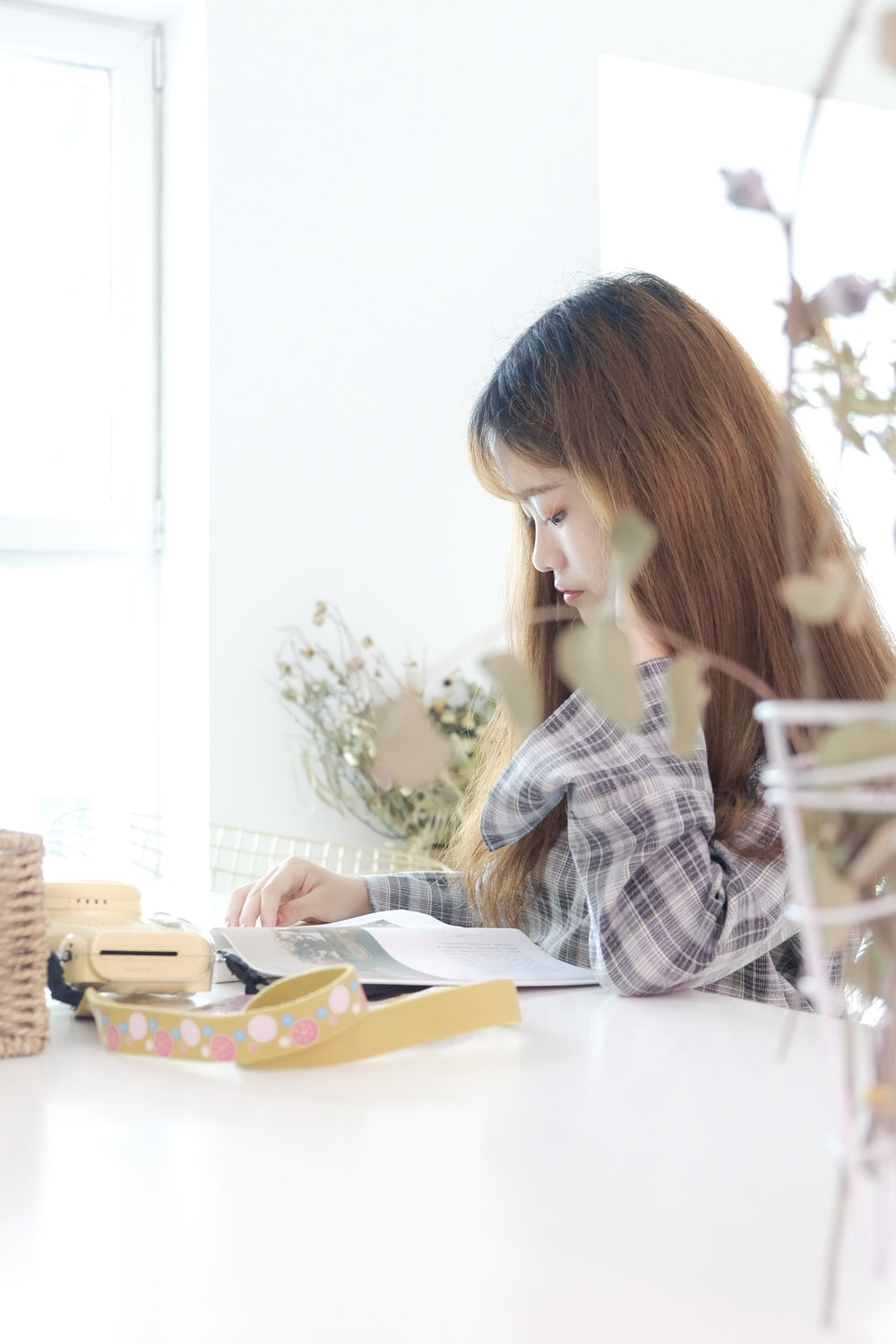 woman reading book at table