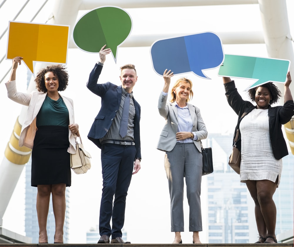 four people holding bubble chat boards