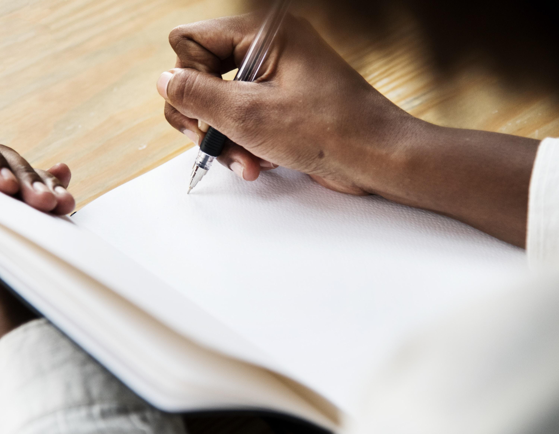person using black ballpoint pen