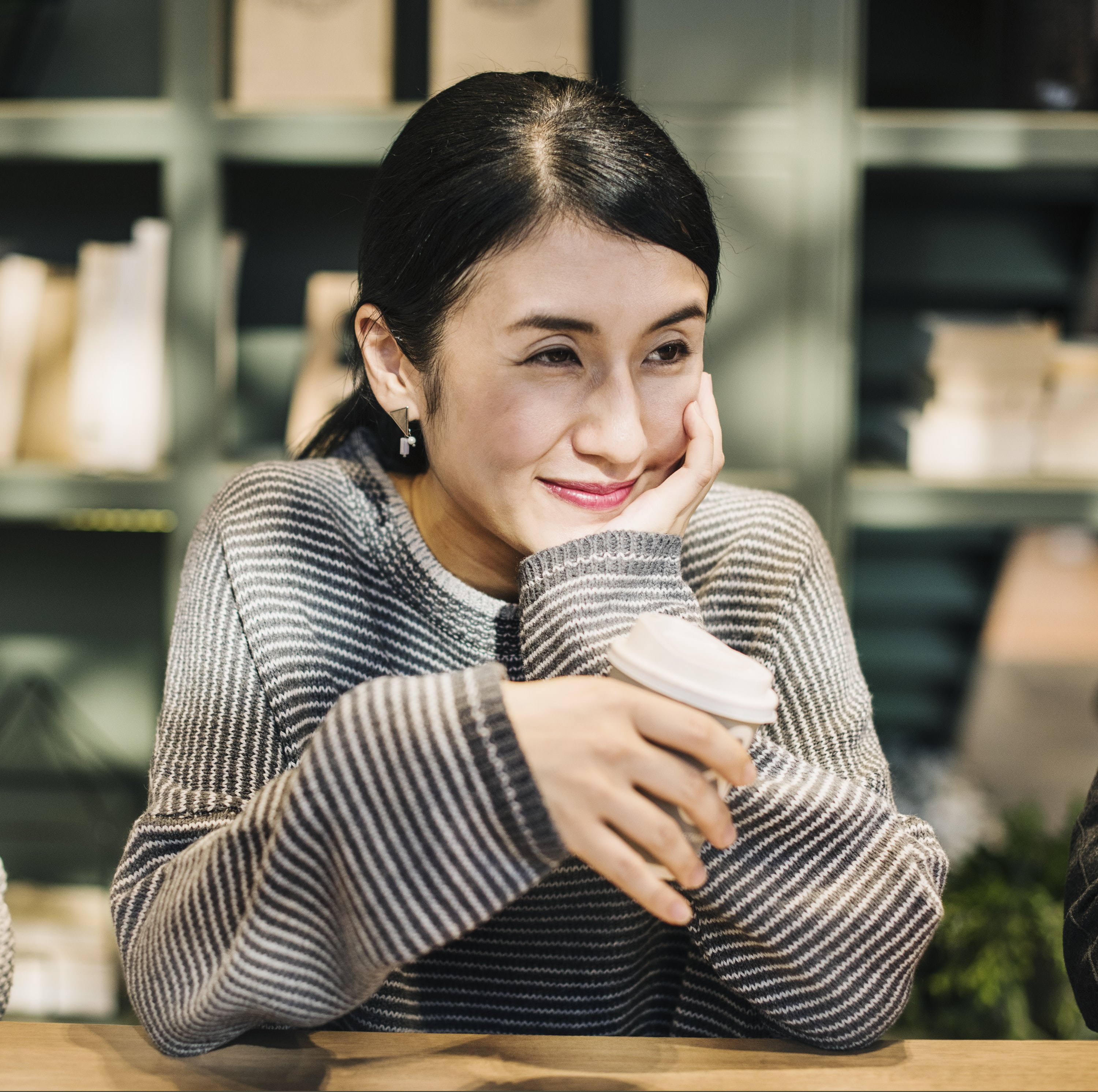 woman holding white disposable cup smiling