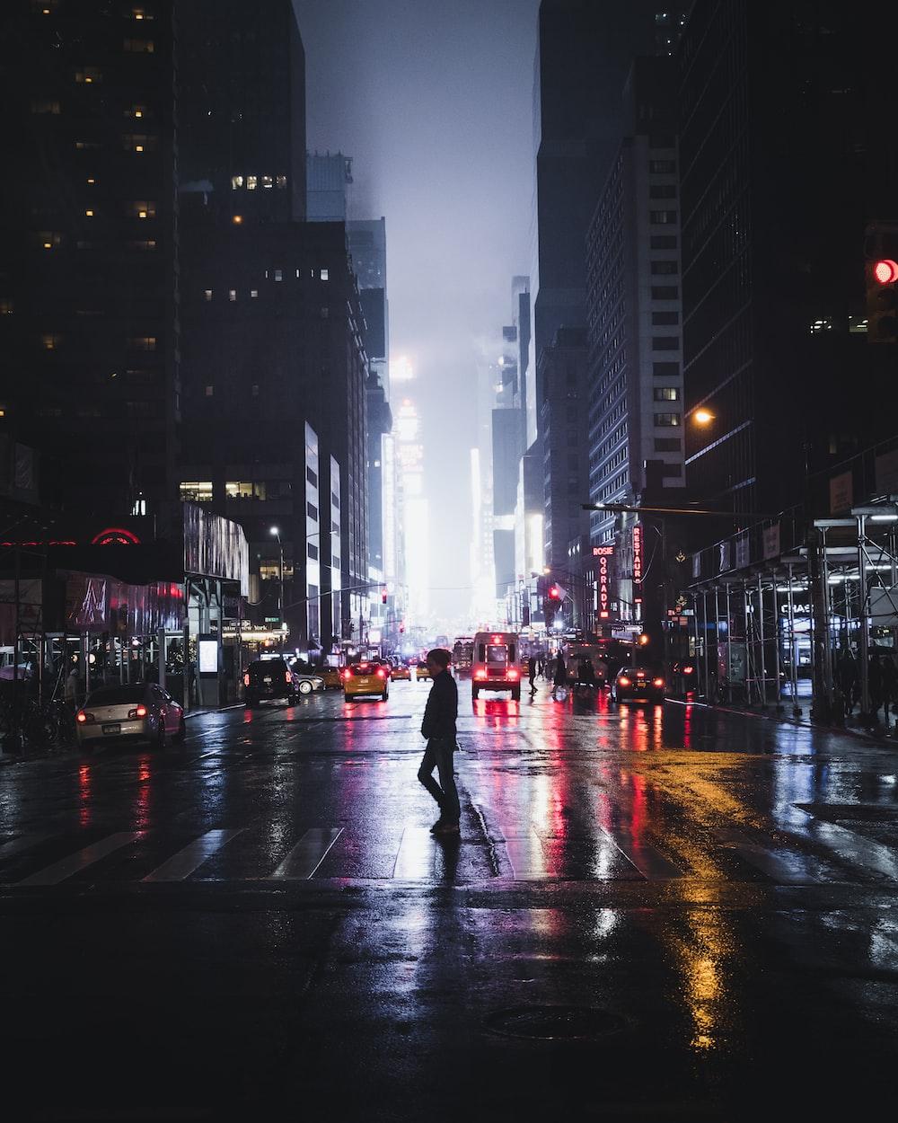 man standing between road