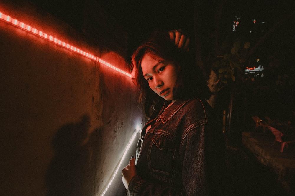 woman wearing blue denim jacket standing beside red LED