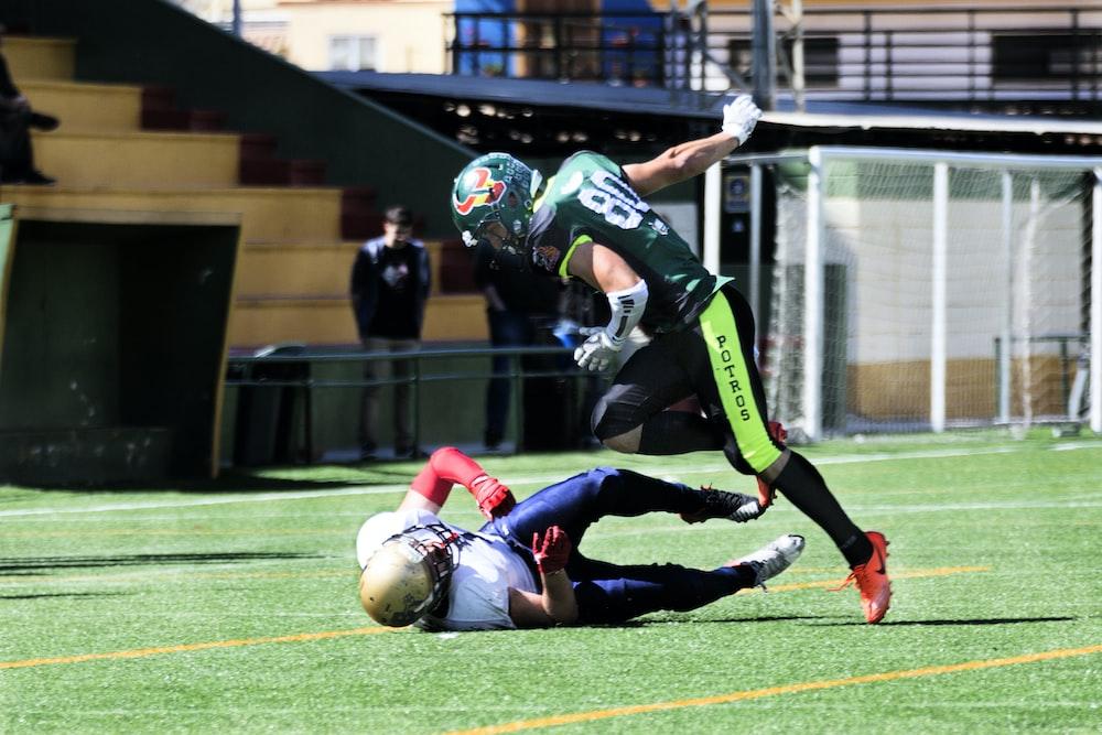 two men playing football during daytime
