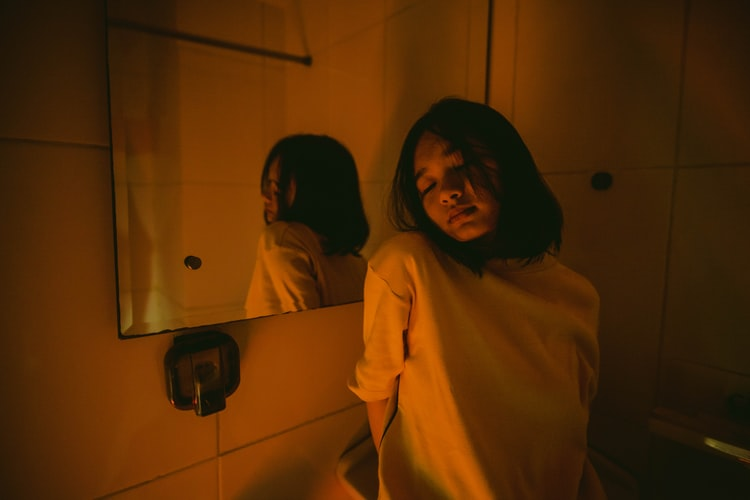 A photo of a young woman in a bathroom, the lighting is very orange and she is leaning against the sink looking generally unimpressed or lacking meaning in life.