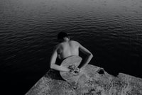 man with round mirror on his back at the edge of rock island facing body of water