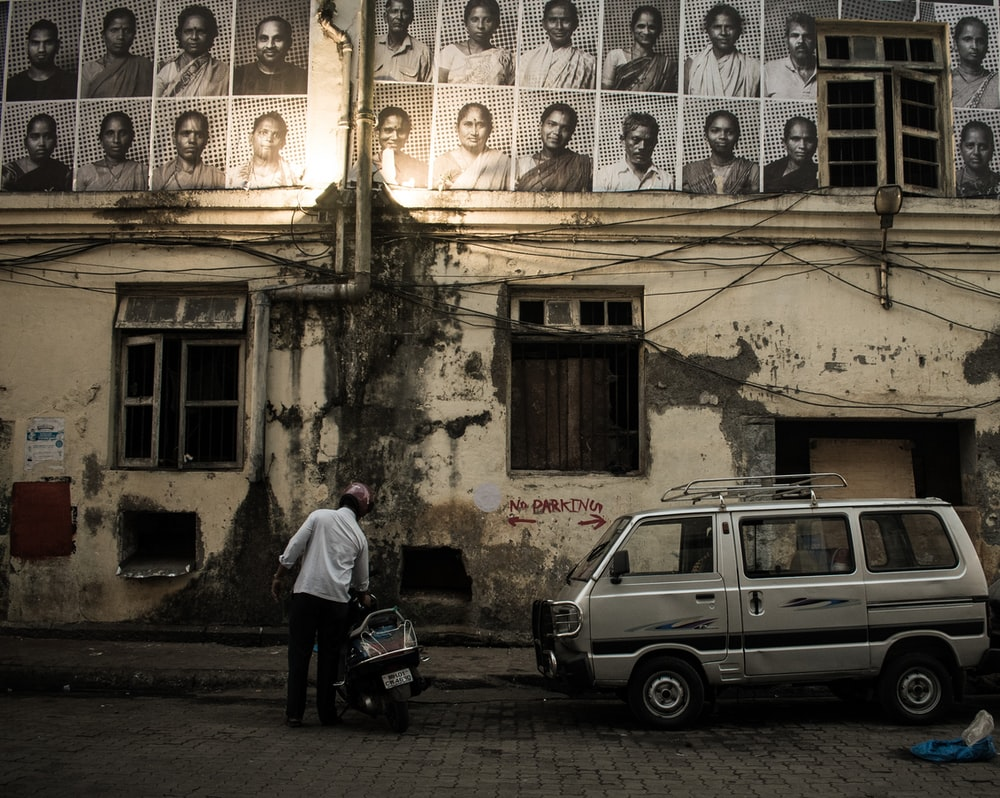 man in white shirt beside black motor scooter looking up at sketch portraits hanged on building wall