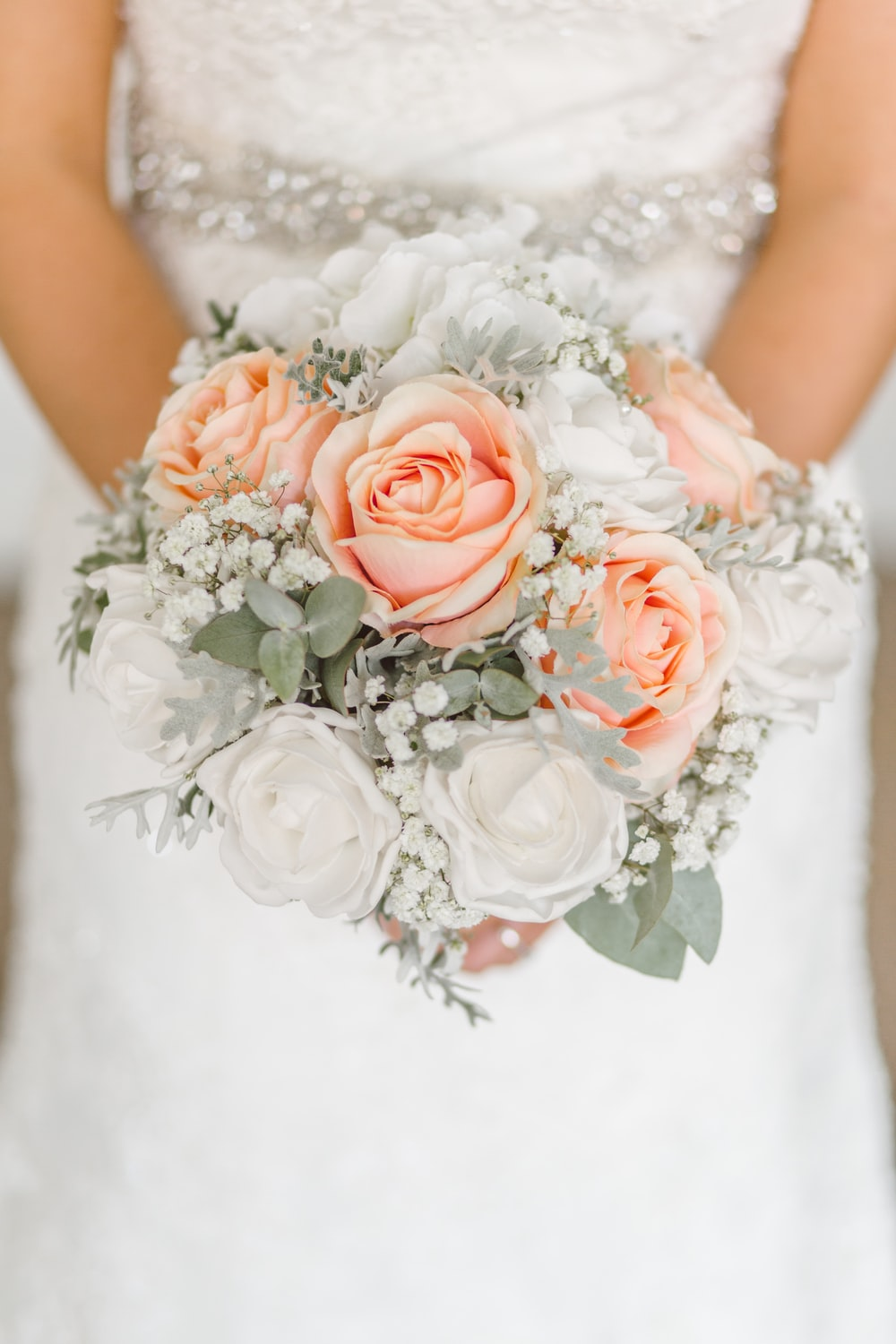 woman holding white and pink rose flower bouquet