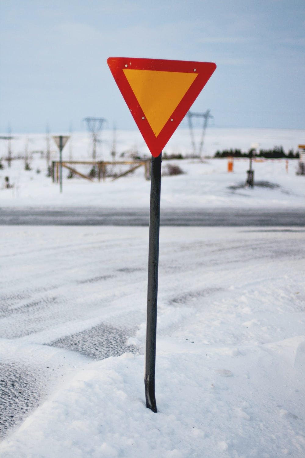 triangle road sign beside road covered with snow
