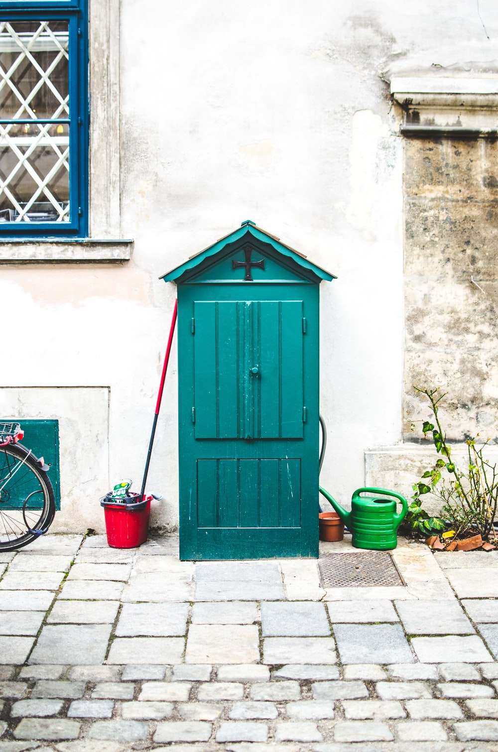 green tool shed beside wall