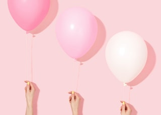 person holding pink and white balloon