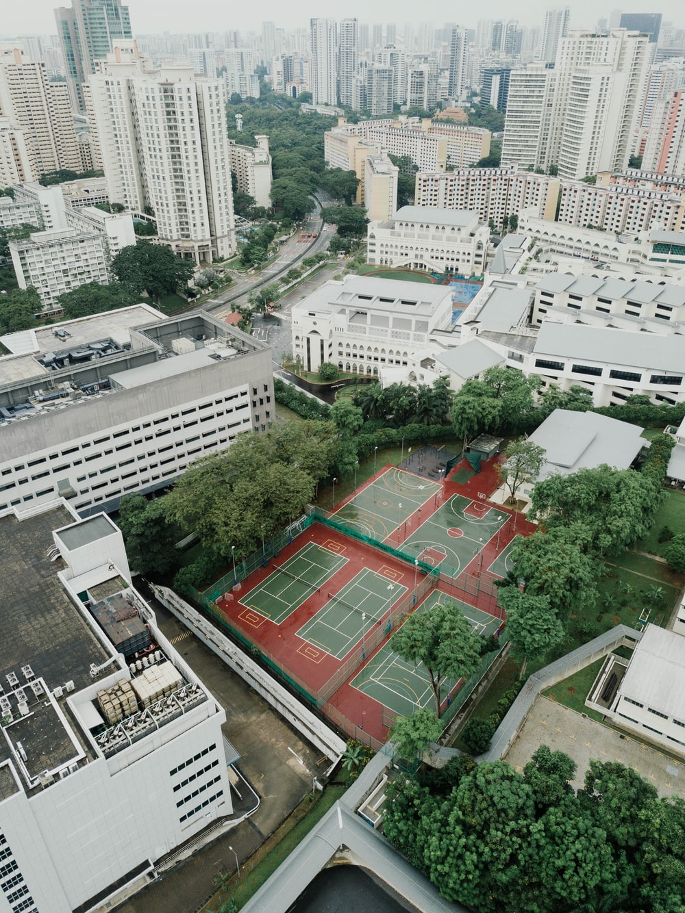 aerial photography of basketball and tennis court in the middle of high-rise buildings