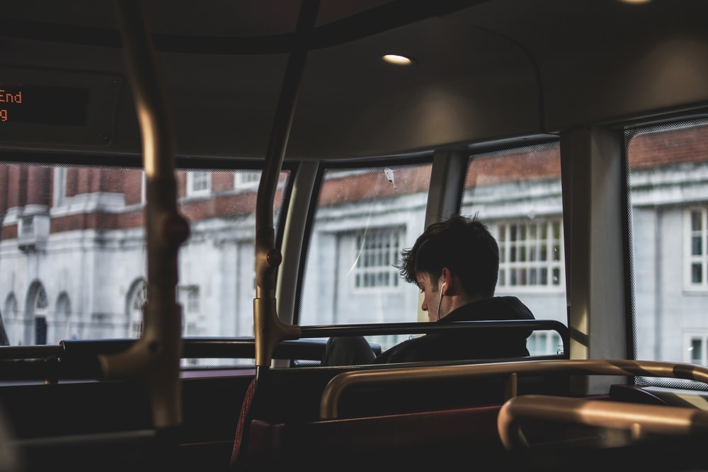 man inside bus using earphones