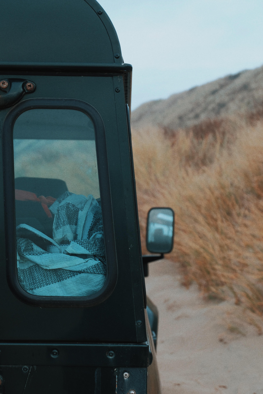 closeup photo of black vehicle near dried grass