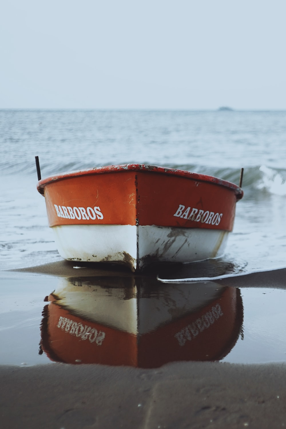 red and white Barboros boat on seashore