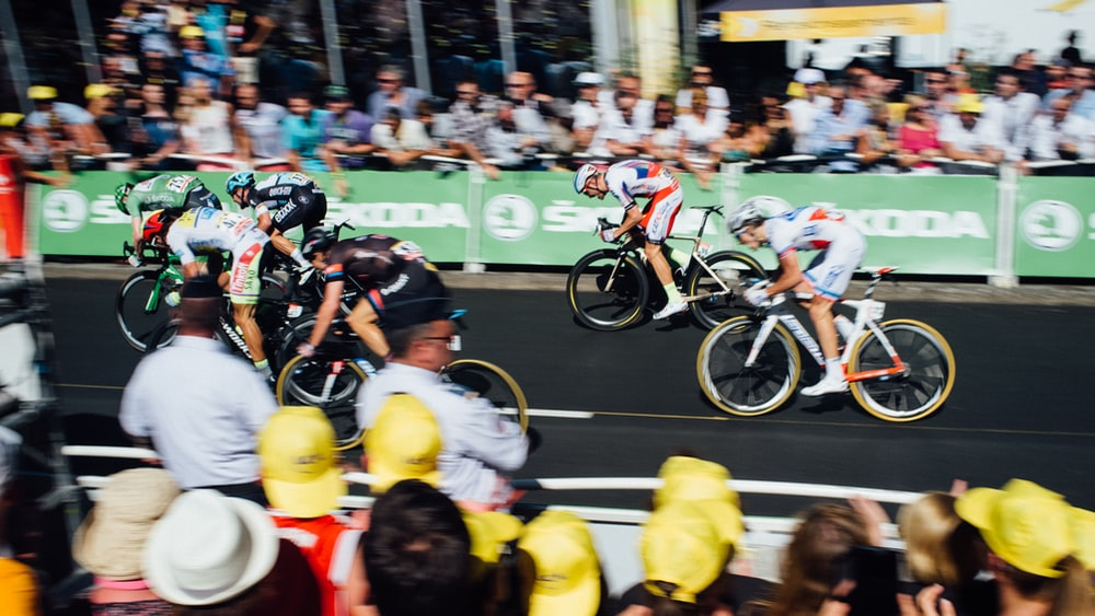 group of people watching cyclist racing