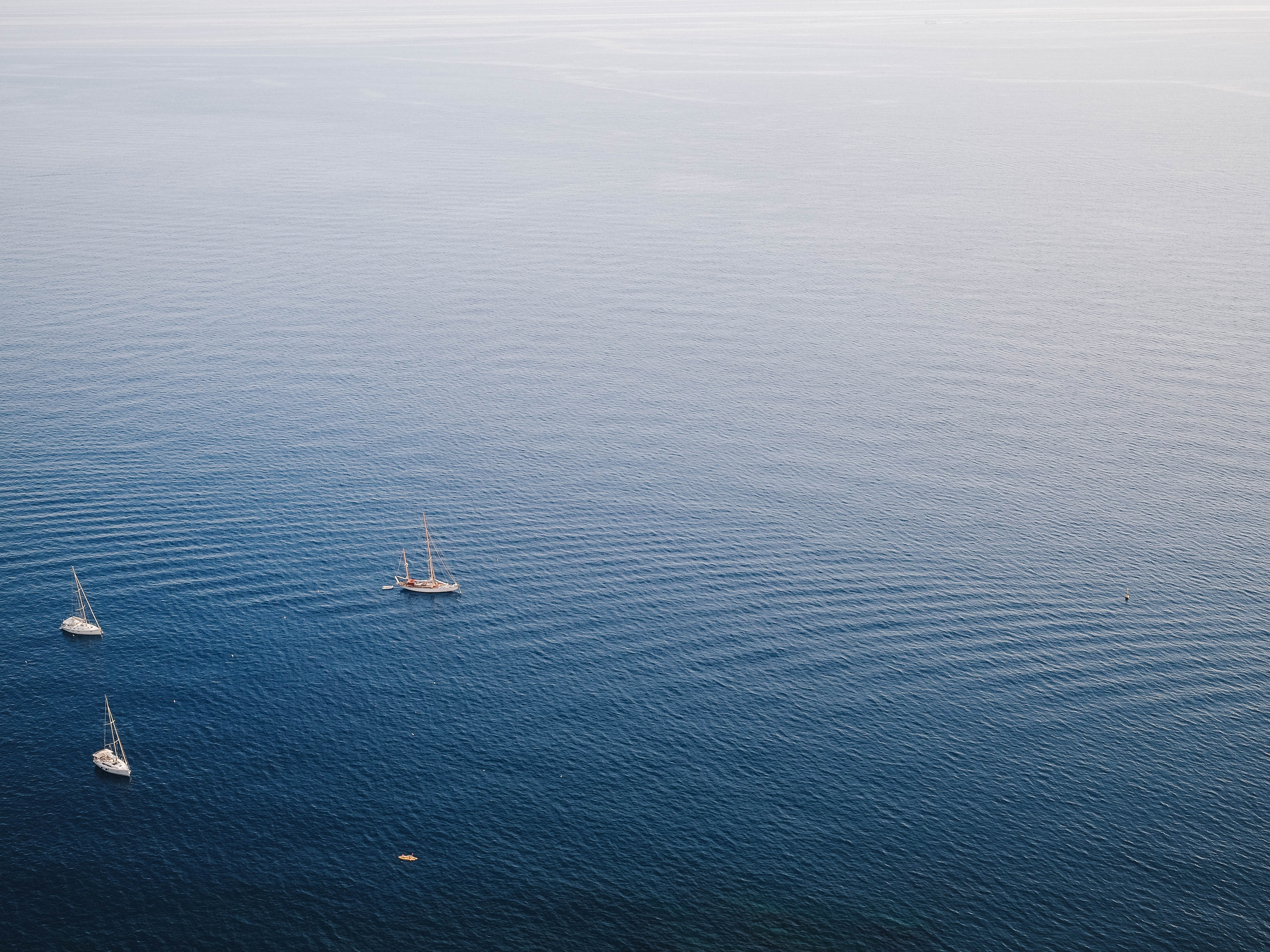 aerial photo of a body of water and fishing vessels