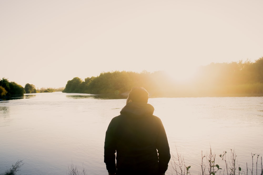 sepia tone photo of man standing in front of body of water