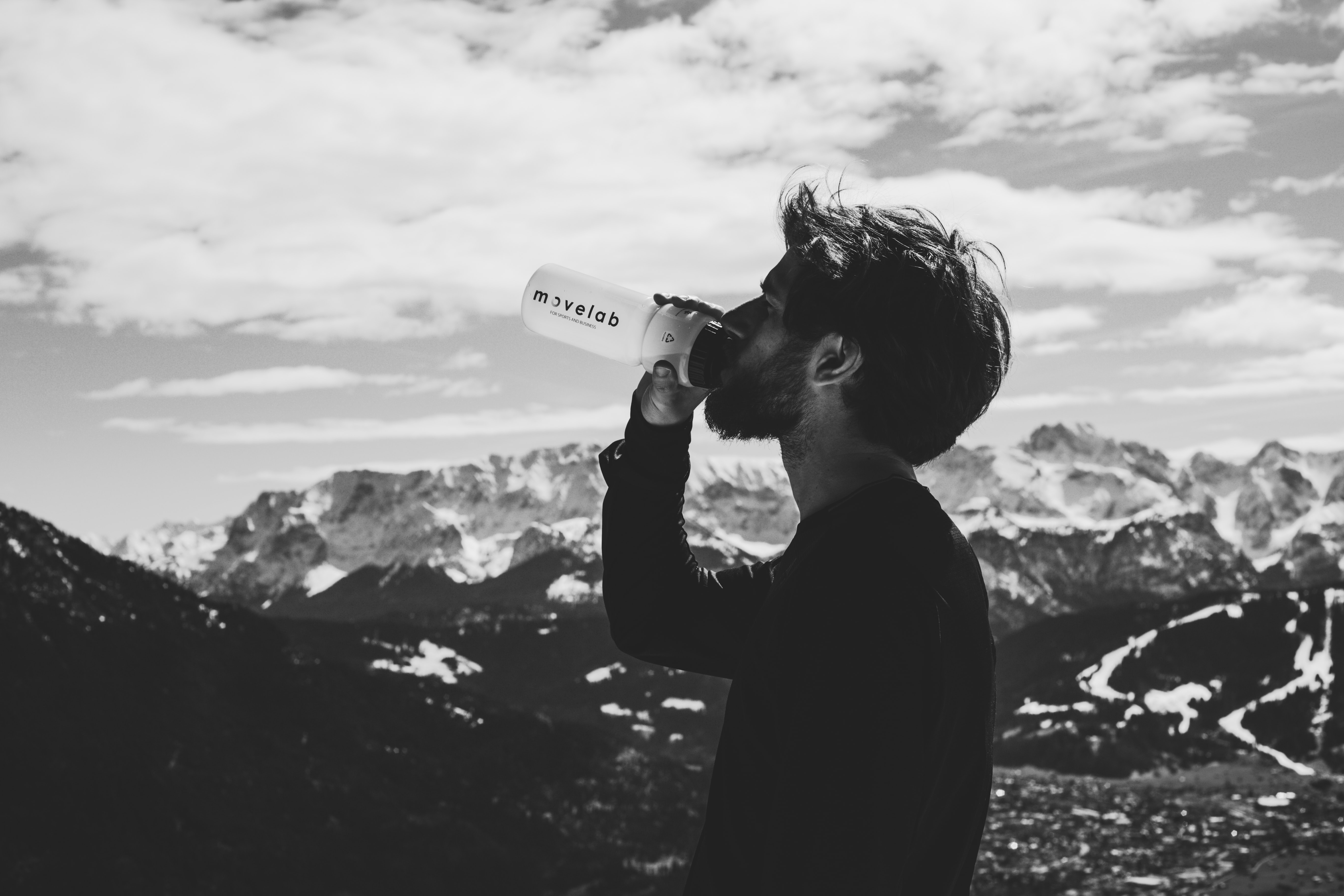 man drinking water on top of mountian