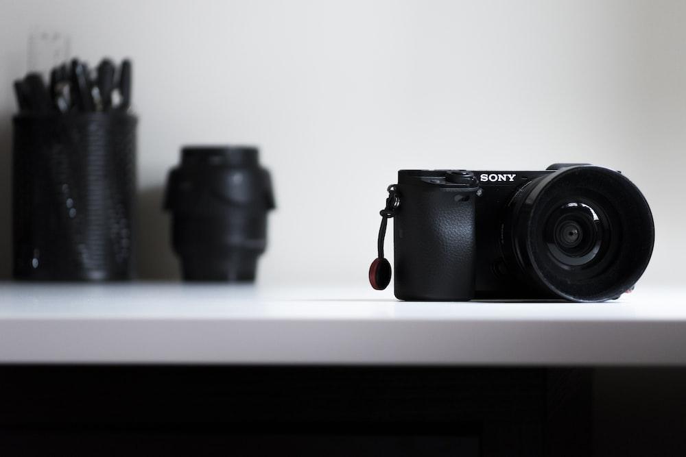black Sony DSLR camera on white desk