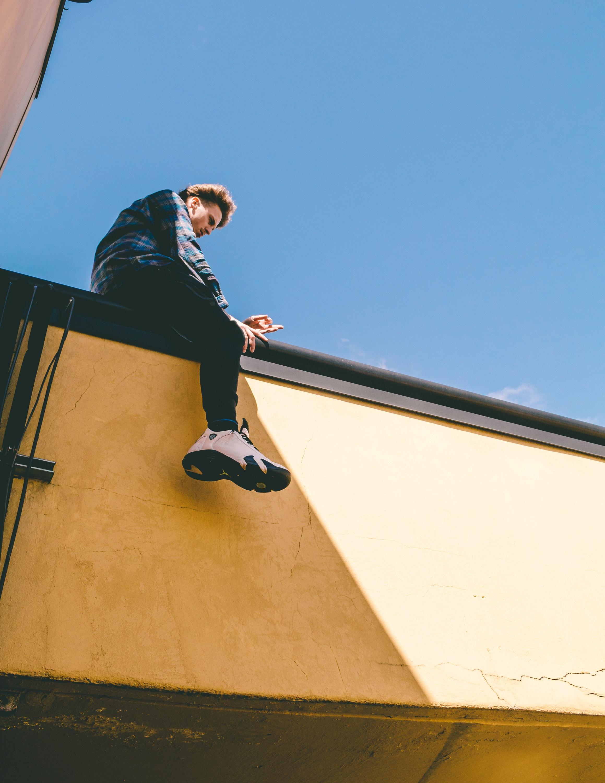 man sitting on roof under blue sky
