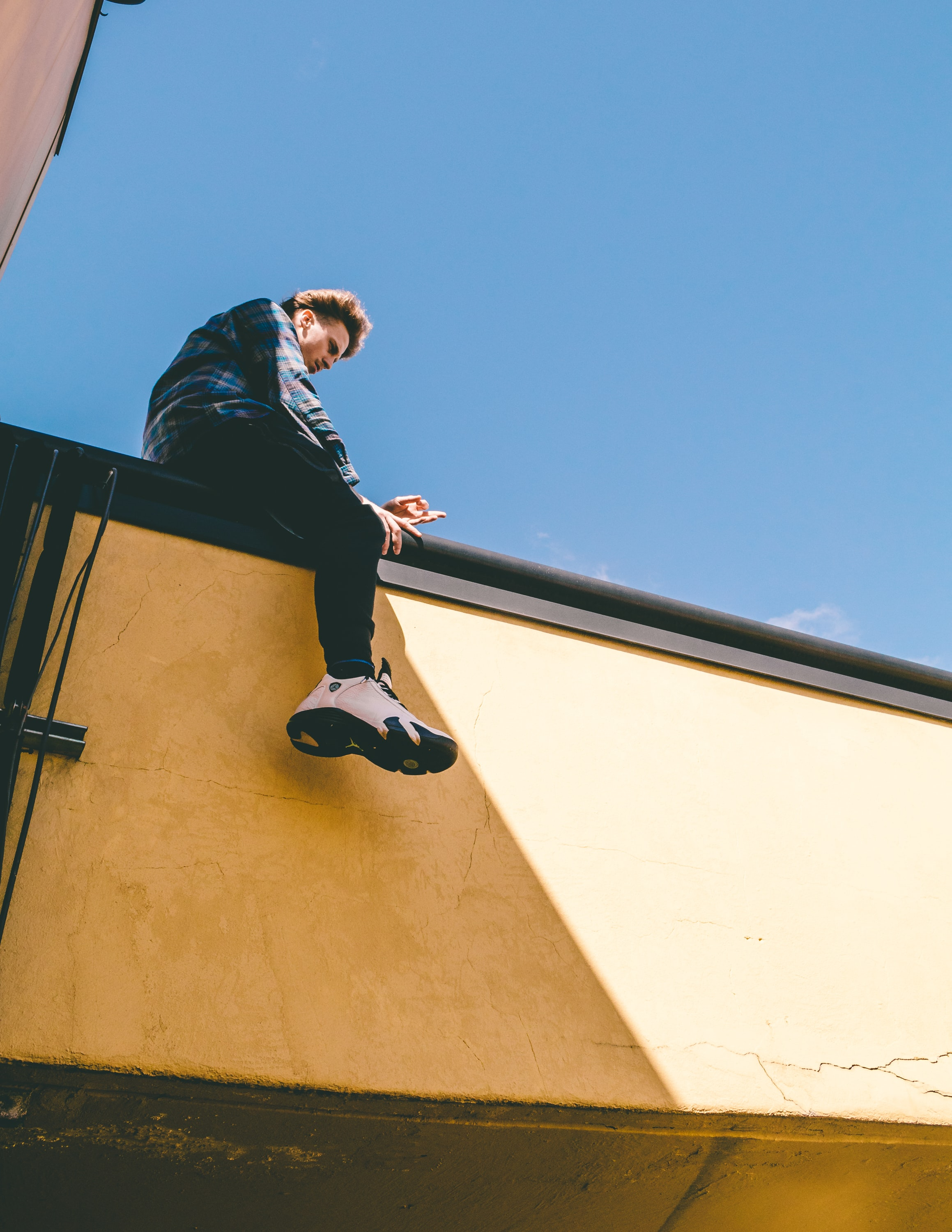 man sitting on roof under blue sky