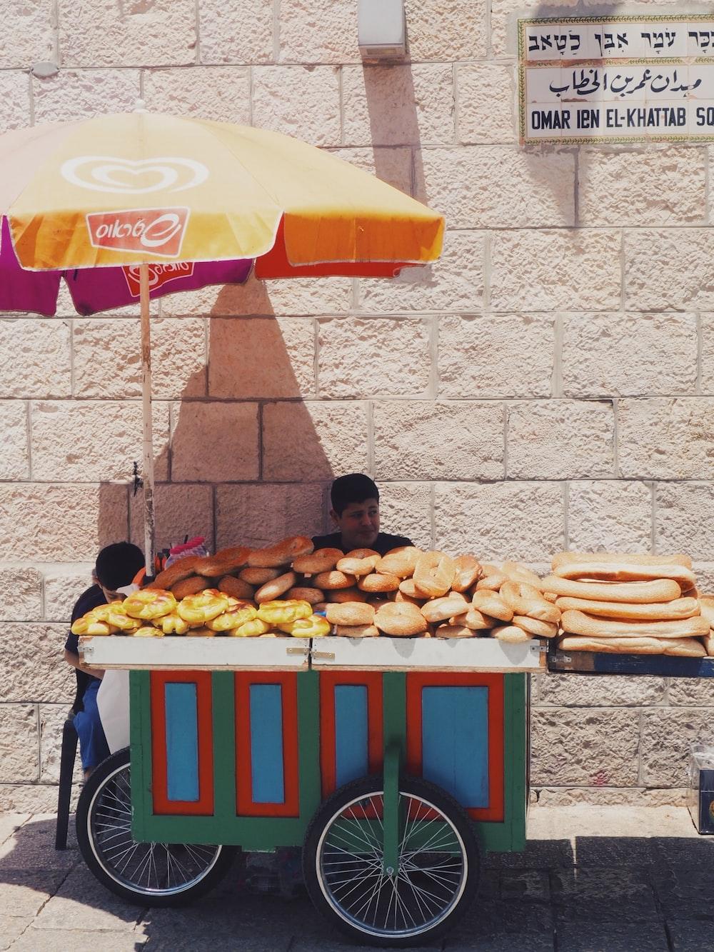 man seating beside food cart