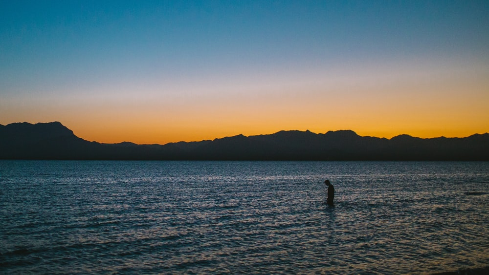 silhouette photo of person on body of water during sunset