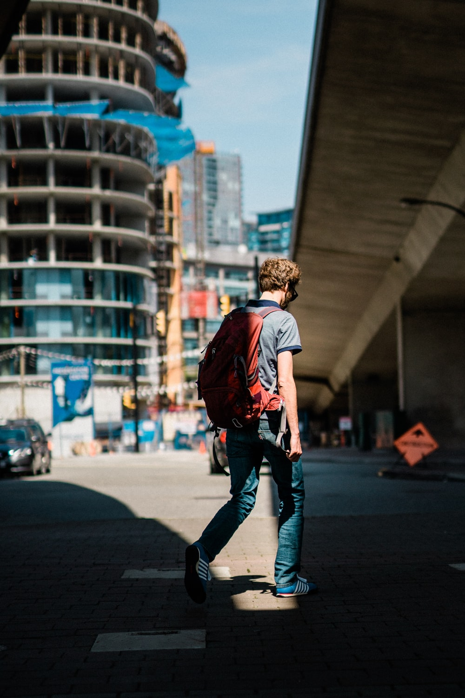 man walking on road near building