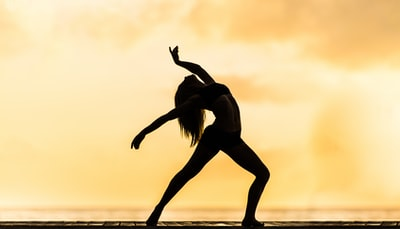 silhouette of woman making yoga pose movement teams background
