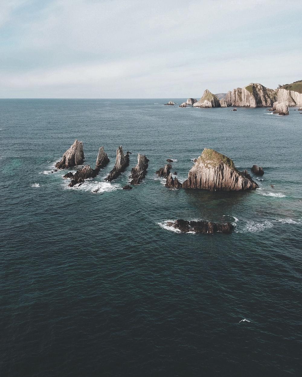 brown rock in the middle of ocean