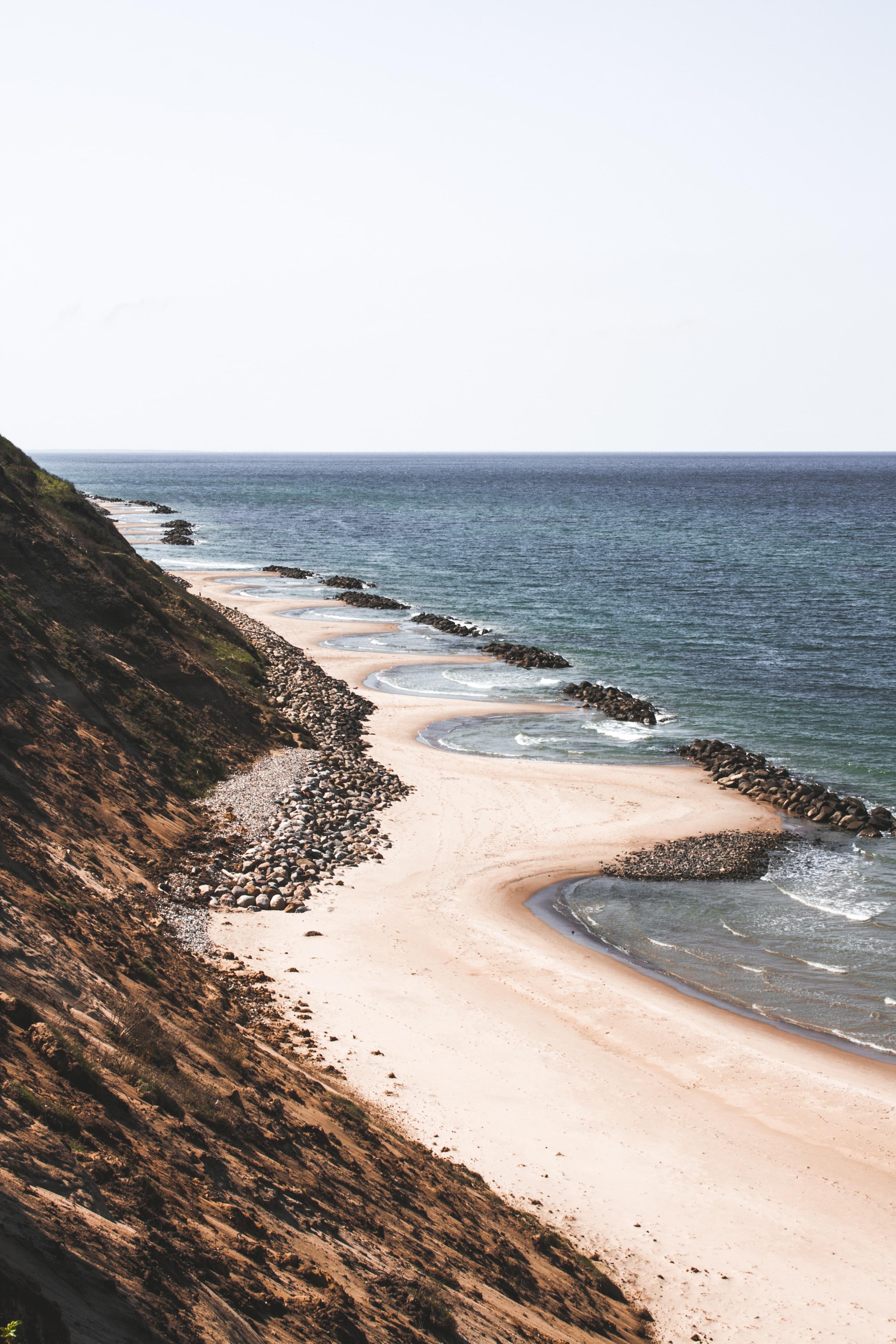 seashore near cliff during daytime