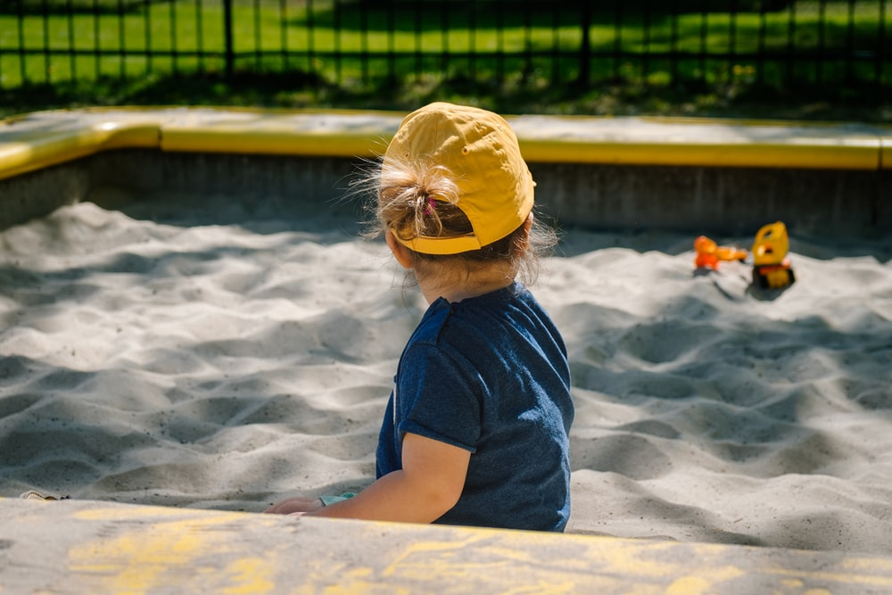 girl playing on sand box