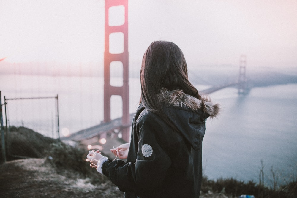 woman wearing parka jacket standing near San Francisco Bridge
