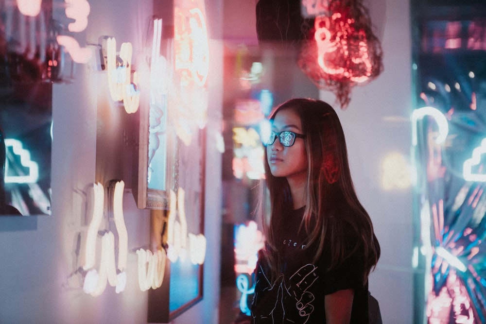 woman standing beside neon signs