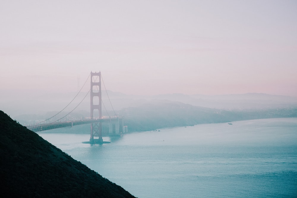 red suspension bridge filled with fog