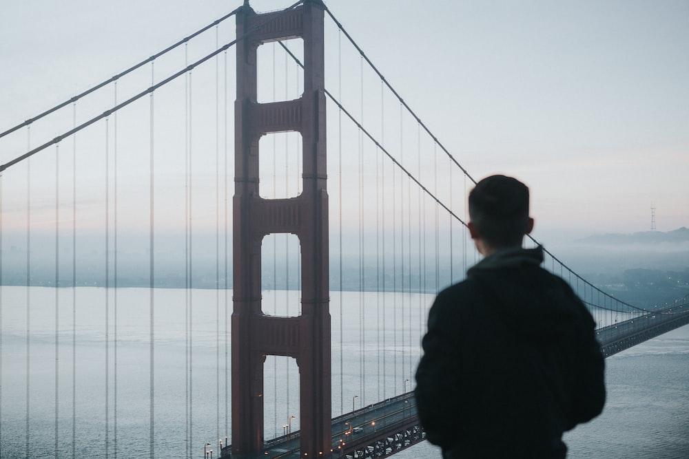 man facing Golden Gate Bridge during daytime