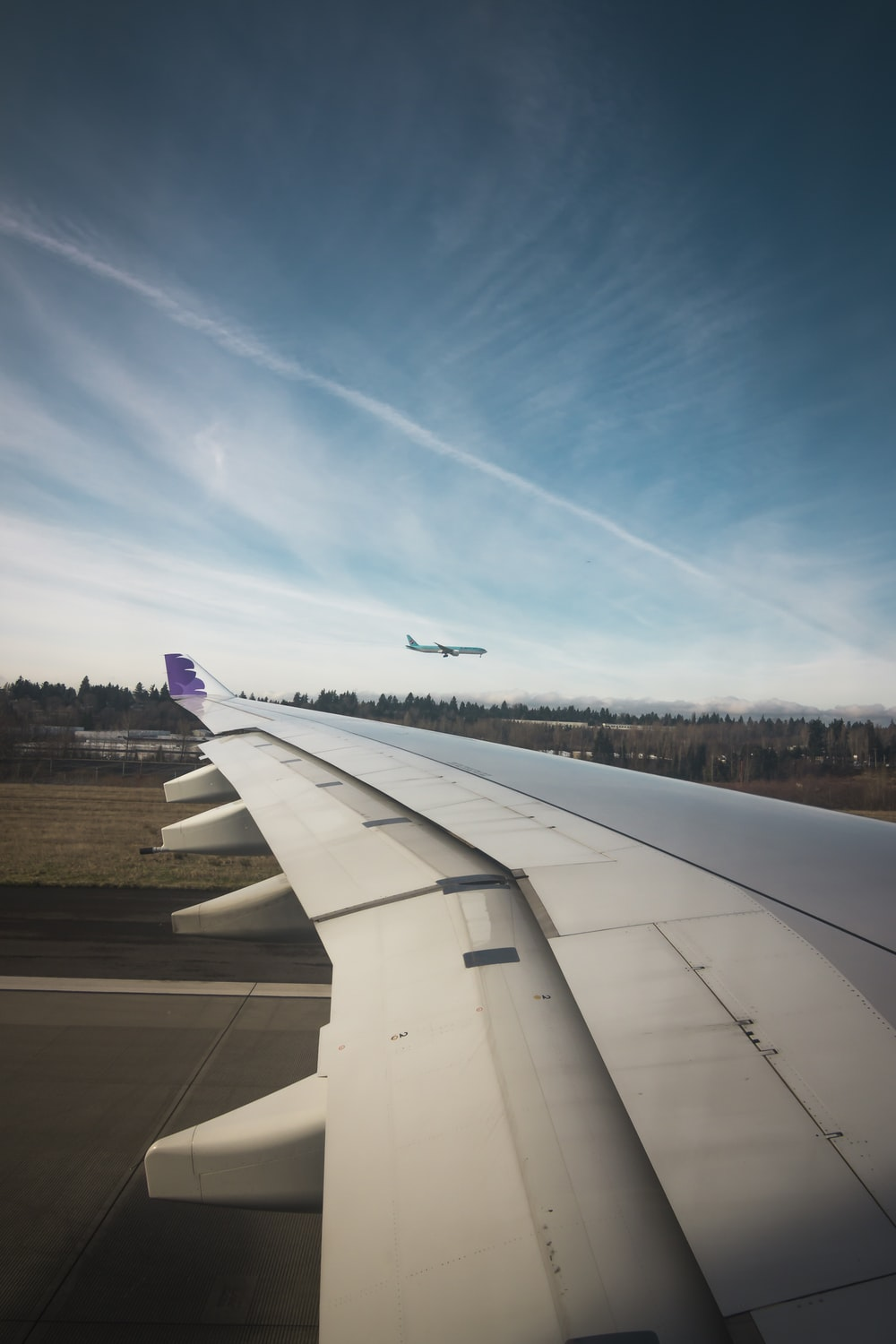 airplane wing under blue and white sky